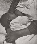 Photography :20th Century , TINA MODOTTI (American, 1896-1942). Baby Suckling Mother, circa 1927. Vintage gelatin silver. 8-1/2 x 7-1/4 inches (...