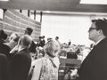 Photography :20th Century , GARRY WINOGRAND (American, 1928-1984). Investor Richard Rapek Among Other Stockholders Reading Latest Prices at Merrill Ly...