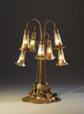 """Lighting:Lamps, TIFFANY STUDIOS. A Seven-Light """"Lily"""" Favrile Glass and Gilt Bronze Table Lamp, circa 1910. Shades engraved: L.C.T. Favril..."""
