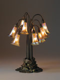 """Lighting:Lamps, TIFFANY STUDIOS. A Ten-Light """"Lily"""" Favrile Glass and Bronze Table Lamp, circa 1910. Shades engraved: L.C.T. Favrile. Po..."""