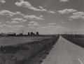 Photography :20th Century , MARION POST WOLCOTT (American, 1910-1990). Highway Showing Grain Elevators and Part of Town of Froid, Montana, August 1941...