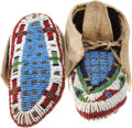 American Indian Art:Beadwork and Quillwork, A PAIR OF PLAINS CHILD'S BEADED HIDE CEREMONIAL MOCCASINS. c. 1890...