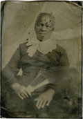 "Photography:Tintypes, Large Tintype of African-American Woman. A large 7"" x 10"" tintypeof an austerely dressed seated woman holding a fan. The im..."