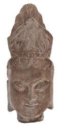 Asian, The Collection of Paul Gregory and Janet Gaynor. AFINELY-CARVED STONE BUDDHA HEAD . China. 11 inches high (27.9 cm)....