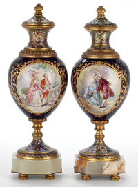 PAIR OF SÈVRES STYLE COVERED URNS IN GILT BRONZE MOUNTS WITH CHAMPLEVÉ ENAMEL France, circa 1900 Signed to...
