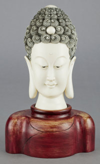 A CHINESE CARVED IVORY AND ENAMEL HEAD OF BUDDHA ON CARVED WOODEN BASE 20th century 11-5/8 inches high (29.5