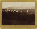 """Photography:Official Photos, CROW ENCAMPMENT IN WESTERN MONTANA. Sepia-toned image measures 7"""" x5"""" and depicts a large Crow camp on Pryor Creek, named a... (Total:1 Item)"""