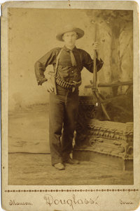 DOUGLASS CABINET PORTRAIT OF YOUNG MAN WITH GUNS. Full-length studio image of a young man proudly showing off his shotgu...