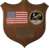 "U.S. Flag Carried on the Moon by Neil Armstrong! Affixed to a 12"" x 14"" wooden shield plaque is a 6"" x 3..."