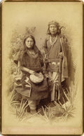 Photography:Cabinet Photos, CHIRICAHUA APACHES WITH BOWL AND BEAUTIFUL CONCHO BELT ca 1880sBavetentio and his squaw Chiricahua Apaches. Squaw is holdin...(Total: 1 Item)