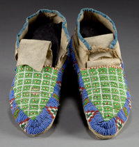 A PAIR OF SIOUX BEADED HIDE MOCCASINS c. 1910