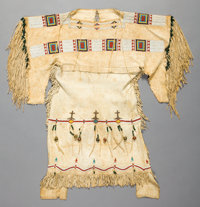 A CHEYENNE GIRL'S BEADED AND FRINGED HIDE DRESS c. 1900