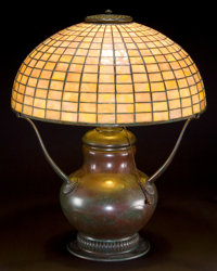 TIFFANY STUDIOS GEOMETRIC GLASS SHADE WITH HUBBELL BASE Bronze lamp base with tiled leaded glass shade in a rose