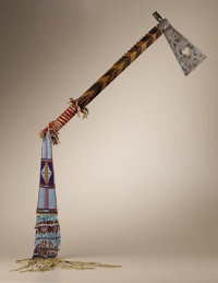 Crow Tomahawk with heart cutout and beaded and fringed pendant Circa 1890 Length 51 1/4 in. overall; Length 8 1/2 in. th...