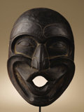 Native American:War Shirts/Garments, Kwakiutl Dzoonokwa Mask. Circa 1970. Height 13 1/4 in. Width 9 in..This carved and black painted cedar wood mask represen...