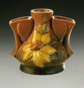 Ceramics & Porcelain, American:Modern  (1900 1949)  , AN AMERICAN ART POTTERY VASE. Roseville. The triple vase formmolded with a flower in yellow and green on a matte tan glaz...