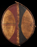 African, AN EAST AFRICAN PAINTED LEATHER SHIELD . Early 20th century. 32inches high x 24 inches wide (81.3 x 61.0 cm). ...