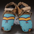 American Indian Art:Beadwork and Quillwork, A PAIR OF ASSINIBOINE BEADED HIDE MOCCASINS. c. 1910...